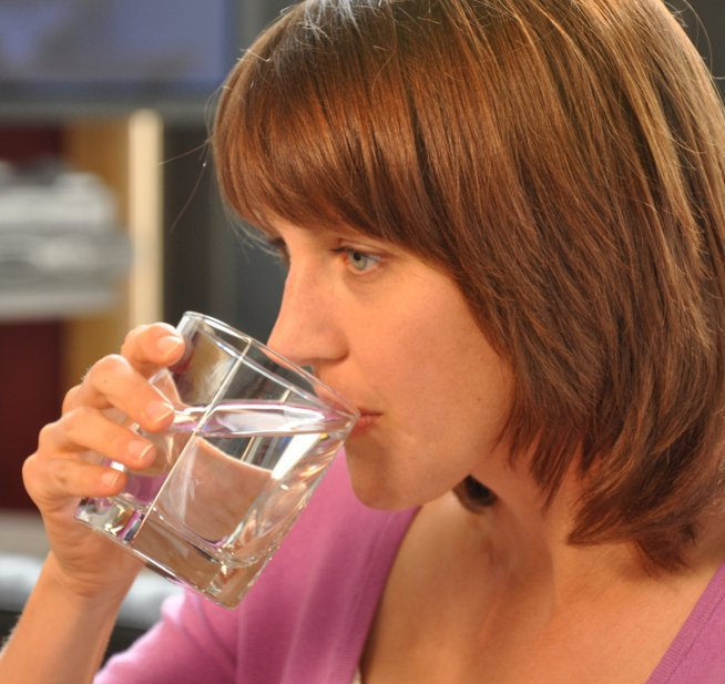 Eating and drinking after a tooth extraction. Woman drinking from a glass
